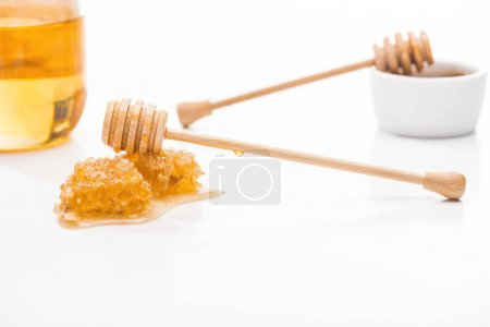 Photo for Selective focus of honeycomb with sweet honey and wooden honey dippers near jar isolated on white - Royalty Free Image
