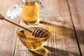 "Постер, картина, фотообои ""jars with honey and honey dipper on wooden table in sunlight"""