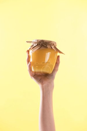 Photo for Cropped view of woman holding glass jar with delicious sweet honey in hand isolated on yellow - Royalty Free Image