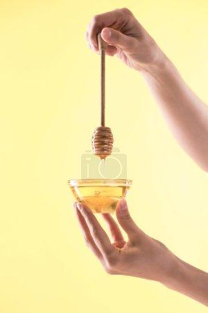 Photo pour Vue recadrée de femme retenant le bol en verre et le dipper en bois avec le miel d'esgouttement isolé sur le jaune - image libre de droit