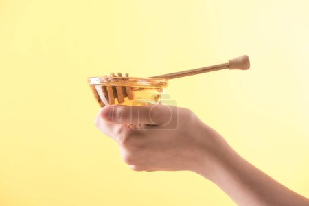 Photo for Cropped view of woman holding glass bowl with honey and wooden dipper isolated on yellow - Royalty Free Image