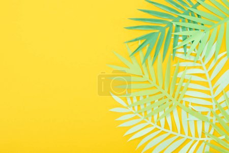 Photo for Top view of paper cut green tropical leaves on yellow bright background with copy space - Royalty Free Image