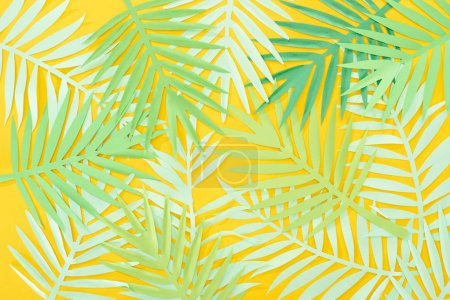 Photo for Top view of paper cut green tropical leaves scattered on yellow bright background - Royalty Free Image