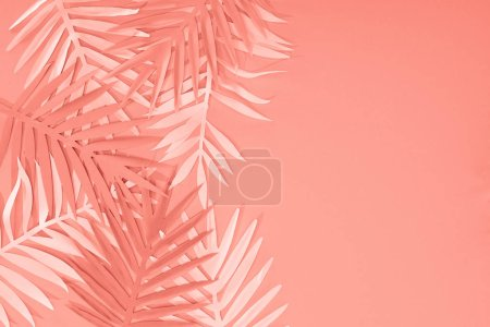 Photo for Top view of coral tropical paper cut palm leaves, minimalistic background with copy space - Royalty Free Image