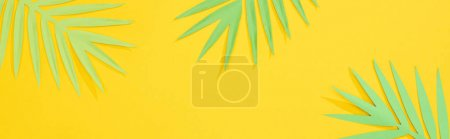 Photo for Top view of paper cut green tropical palm leaves on yellow bright background with copy space, panoramic shot - Royalty Free Image