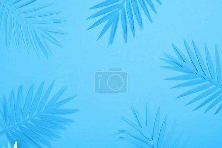 Foto de Vista superior de las hojas de papel en el fondo minimalista azul con espacio de copia - Imagen libre de derechos