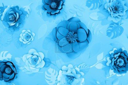 Photo pour Vue supérieure des feuilles et des fleurs de papier sur le fond minimaliste bleu - image libre de droit