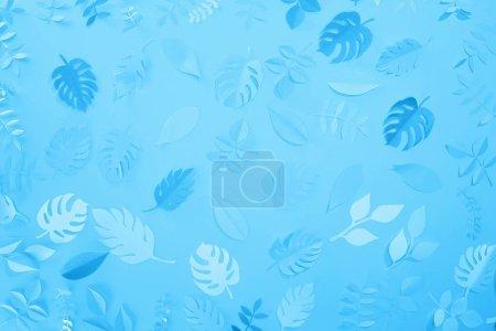 Photo pour Vue supérieure des feuilles coupées de papier sur le fond minimaliste bleu - image libre de droit