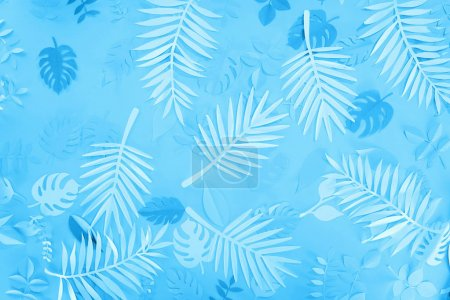 Photo for Top view of exotic paper leaves on blue minimalistic background - Royalty Free Image