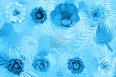 Foto de Vista superior de hojas cortadas de papel y flores sobre fondo minimalista azul - Imagen libre de derechos
