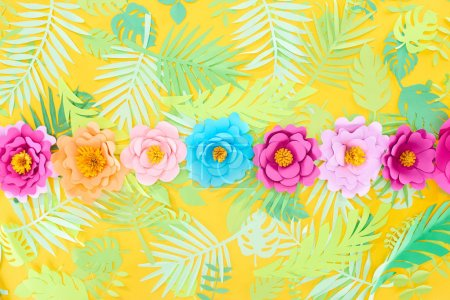flat lay with paper cut multicolored flowers in row on tropical leaves on yellow bright background