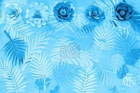Foto de Vista superior de hojas exóticas de papel y flores sobre fondo minimalista azul - Imagen libre de derechos