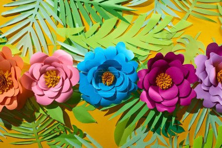 Photo for Flat lay with paper cut multicolored flowers on tropical leaves on yellow bright background - Royalty Free Image