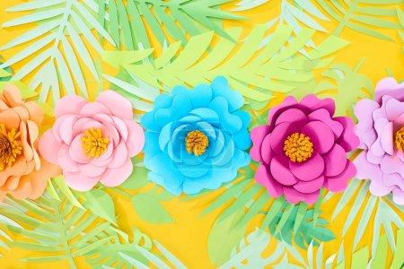 Photo pour Plat s'est couché avec le papier coupé des fleurs multicolores sur des lames tropicales sur le fond lumineux jaune - image libre de droit