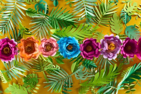 Photo for Flat lay with paper cut flowers on tropical leaves on yellow bright background - Royalty Free Image