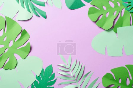 Photo for Top view of green paper cut tropical leaves on violet background with copy space - Royalty Free Image