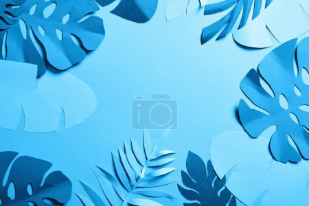 Photo for Paper cut exotic leaves on blue minimalistic background with copy space - Royalty Free Image