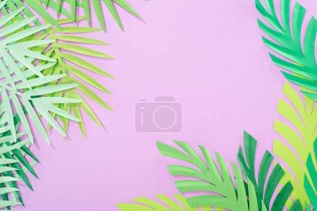 Foto de Vista superior del papel verde cortado hojas tropicales sobre fondo violeta con espacio de copia - Imagen libre de derechos