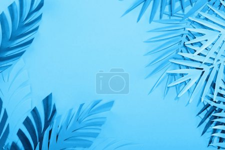 Photo for Frame of paper leaves on blue minimalistic background with copy space - Royalty Free Image