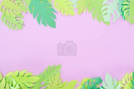 Photo pour Vue supérieure du papier vert coupé feuilles tropicales sur le fond violet avec l'espace de copie - image libre de droit