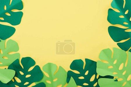 Photo pour Vue supérieure du papier coupé les feuilles tropicales vertes sur le fond lumineux jaune avec l'espace de copie - image libre de droit