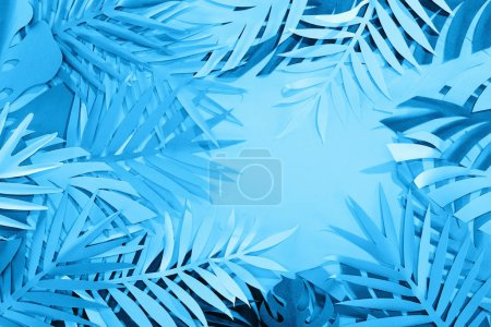 Photo for Top view of paper leaves on blue minimalistic background with copy space - Royalty Free Image