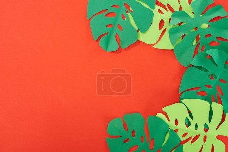 Photo for Top view of green paper cut tropical leaves on bright red background with copy space - Royalty Free Image