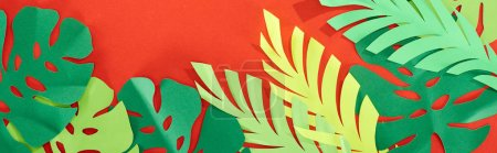 top view of green paper cut tropical leaves on bright red background with copy space