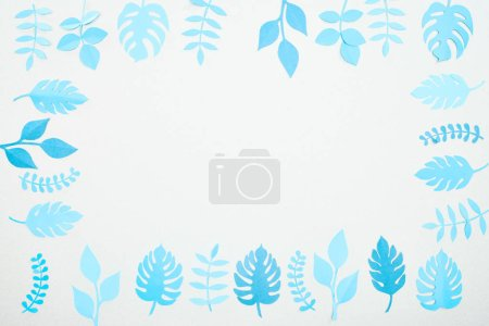 Photo for Top view of blue paper cut tropical leaves isolated on white with copy space - Royalty Free Image