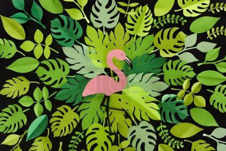 top view of paper cut green leaves with flamingo isolated on black, background pattern