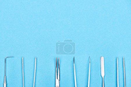 Photo pour Vue du haut de l'ensemble avec des instruments dentaires métalliques isolés sur le bleu - image libre de droit
