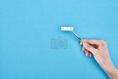 Photo pour Vue recadrée d'une femme tenant une pince à épiler avec coton sur fond bleu - image libre de droit