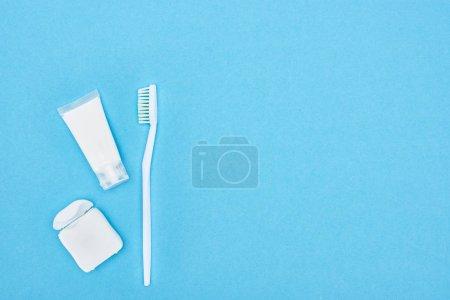 Photo pour Vue du dessus de la brosse à dents et du dentifrice près des dents fil dentaire isolé sur bleu - image libre de droit