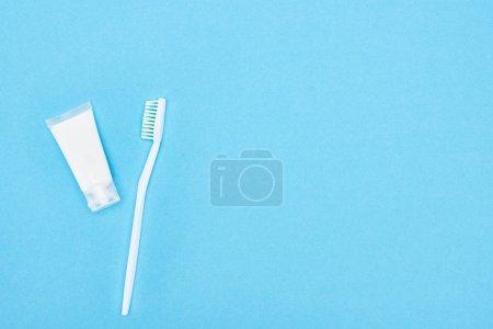 Photo pour Vue du dessus de la brosse à dents blanche et du dentifrice isolés sur bleu - image libre de droit