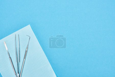 Photo for Top view of stainless dental tools on apron isolated on blue - Royalty Free Image