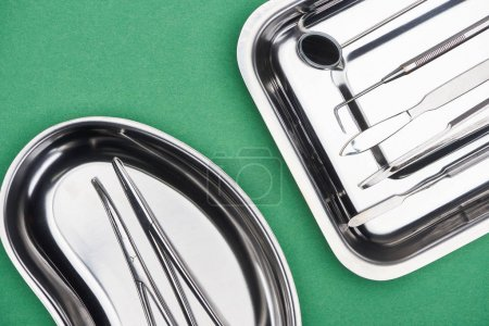 Photo for Top view of set with dental tools in metallic plates isolated on green - Royalty Free Image