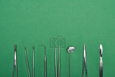 Photo for Top view of set with stainless dental tools isolated on green - Royalty Free Image