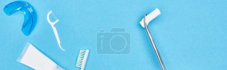 Photo for Panoramic shot of tweezers with cotton pad near toothpaste and toothbrush on blue - Royalty Free Image