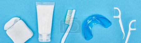 Photo pour Prise de vue panoramique de brosse à dents, dentifrice et fil dentaire près de l'appareil de retenue et les bâtons de fil dentaire isolés sur bleu - image libre de droit
