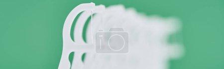 Foto de Foto panorámica de palillos de hilo dental blanco aislado en verde - Imagen libre de derechos