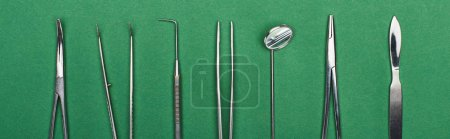 Photo for Panoramic shot of set with stainless dental tools isolated on green - Royalty Free Image