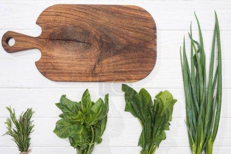 Foto de Vista superior de la tabla de cortar madera y la vegetación en la mesa blanca - Imagen libre de derechos