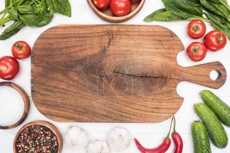 Photo for Top view of cutting board, cherry tomatoes, greenery, chili peppers, salt, cucumbers, garlics and spices - Royalty Free Image