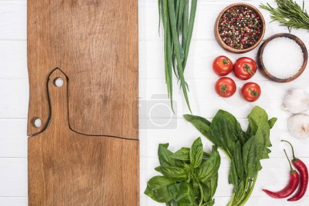 Photo for Top view of cutting boards, cherry tomatoes, greenery, chili peppers, salt, garlics and spices - Royalty Free Image