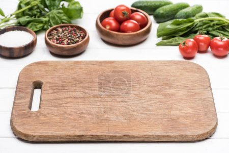 Photo for Cutting board, cherry tomatoes, greenery, cucumbers, salt and spices - Royalty Free Image