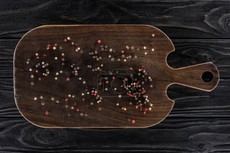 top view of wooden cutting board with spices on table