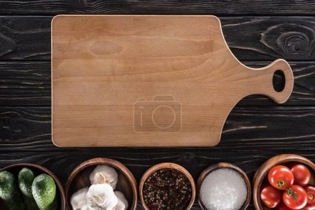 Photo for Top view of cutting board, cherry tomatoes, salt, garlics, cucumbers and spices - Royalty Free Image