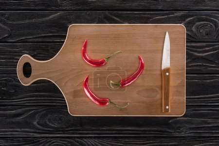 Photo for Top view of cutting board, knife and chili peppers on table - Royalty Free Image