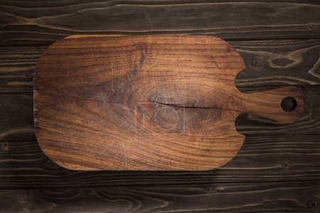 Photo for Top view of wooden cutting board on brown table - Royalty Free Image