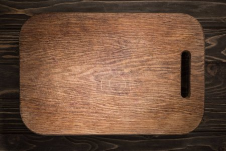 Photo for Top view of wooden cutting board on black table - Royalty Free Image